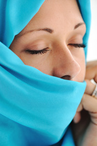 Young beautiful muslim woman in blue scarf