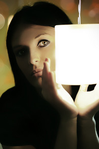 Young beautiful mysterious lady hiding behind the light in her hands with background lights