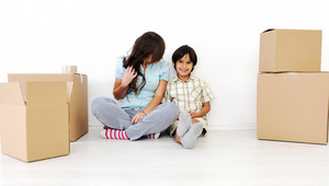 Young beautiful smiling woman and little boy sitting alogside cardboard box