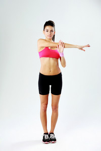 Young beautiful sport woman stretching hands on gray background