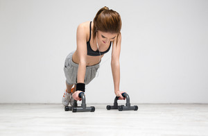 Young beautiful woman doing push ups at gym