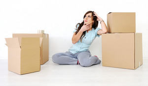 Young beautiful woman sitting leaning on a box and thinking