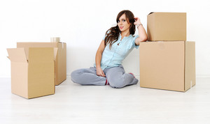 Young beautiful woman sitting leaning on a box looking at camera