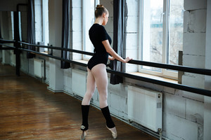 Young beautiful woman standing on poite in ballet class