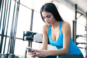 Young beautiful woman using smartphone at gym