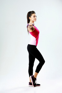 Young beautiful woman with dumbbell working out isolated on gray background