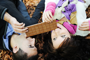 Young beauty girl and her boyfriend eating together chocolate in nature together , fall scene on ground