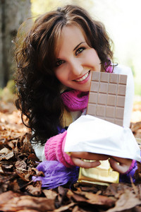 Young beauty girl eating chocolate in nature, fall scene on ground