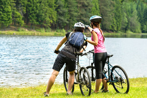 Young bikers standing at lake watching the forest