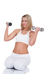 Young blond woman with weights on white background