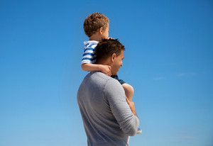 Young boy carried by his father against the blue background