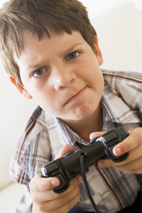 Young boy holding video game controller looking confused