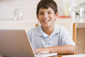 Young boy in kitchen with laptop and paperwork smiling