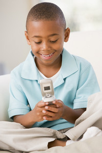 Young boy in living room using cellular phone and smiling