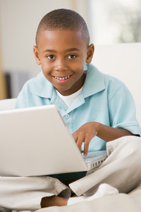 Young boy in living room with laptop smiling