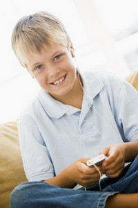 Young boy in living room with MP3 player smiling
