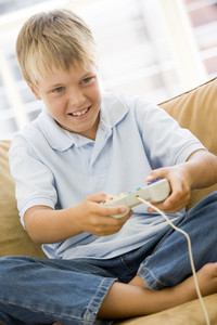 Young boy in living room with video game controller smiling