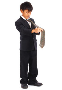 Young Boy In Suit Doing His Tie