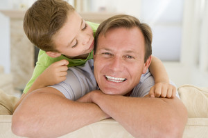 Young boy kissing smiling man in living room