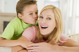 Young boy kissing smiling woman in living room