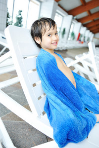 Young boy laying on towel by the edge of the pool
