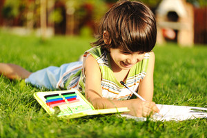 Young boy outdoors on the grass reading a book, writting and drawing