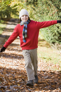 Young boy playing in autumn woods