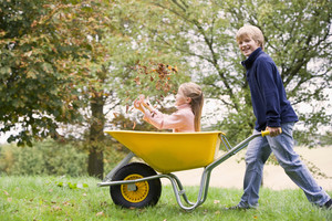Young boy pushing girl in wheelbarrow through autumn woods