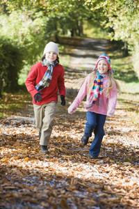 Young boy running along autumn path through woods