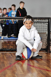 Young boy sitting on basketball, soccer goal and his friends in background