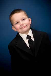 Young boy wearing a suit smiling in front of a blue backdrop.