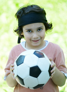 Young boy with football in park