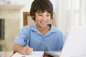 Young boy with laptop doing homework in dining room smiling
