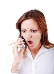 Young brunette with angry expression on face speakin on cell phone