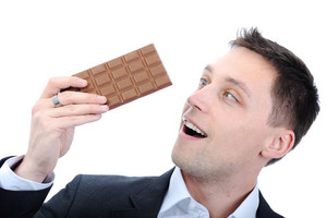 Young business man eating chocolate