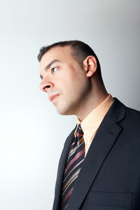 Young business man that looks worried or contemplative isolated over a silver background.
