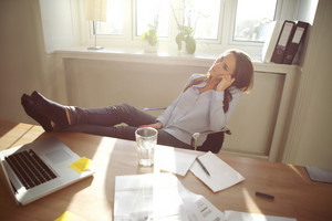 Young business woman sitting at her desk in office with her legs on the desk. Caucasian female relaxing and looking up in home office.