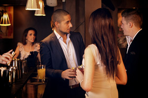 Young businessman hanging out and talking with friends at the bar