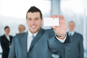 Young businessman holding white card with colleagues in background