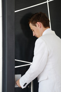 Young businessman standing in modern office lobby and opening door