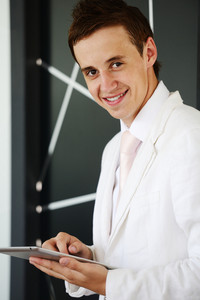 Young businessman standing in modern office lobby