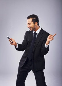 Young businessman with phone dancing out of joy