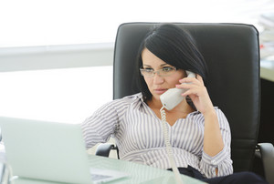 Young businesswoman sitting in an office chair and working, female boss