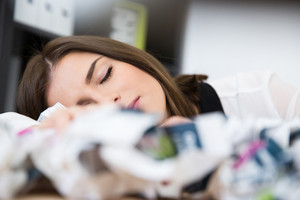 Young businesswoman sleeping on the table with trash papers