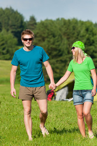Young camping couple hold hands in summer countryside tent