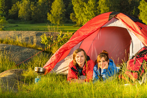 Young camping couple resting and lying in tent sunset countryside