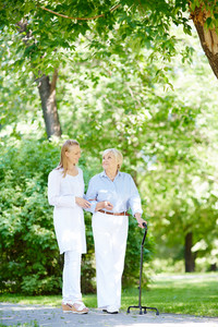 Young caregiver and her senior patient walking out in summer park