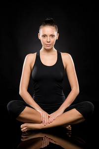 Young Caucasian woman doing yoga legs crossed meditating relaxing pose