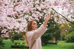 Young caucasian woman picturing blossom flowers with her mobile phone. Attractive woman photographing flowers at the spring garden - Outdoors