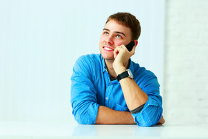 Young cheerful businessman talking on the phone and looking up at copyspace in office